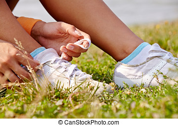 tieing shoe-laces in nature outdoors - woman sitting on...