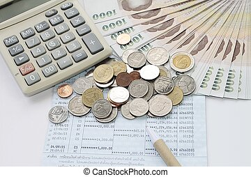 Coins, money, calculator and pen on savings account passbook...