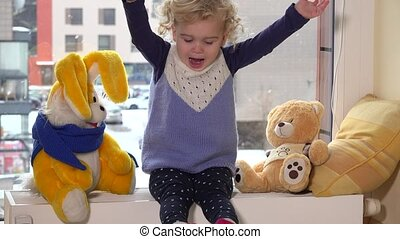 Happy toddler child play with her best friends on radiator near window