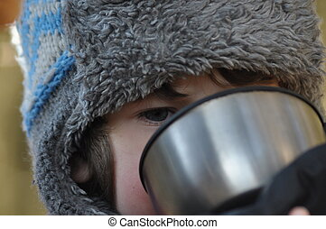 The boy, the child in the forest. Fun in the fresh air. Drinking hot tea from a thermos