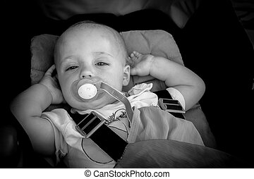 Baby boy in a pushchair - Portrait of a happy and adorable...