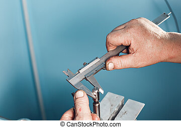 mechanical technician worker hands measuring detail tool after processing at workshop with sliding caliper  manufacturing