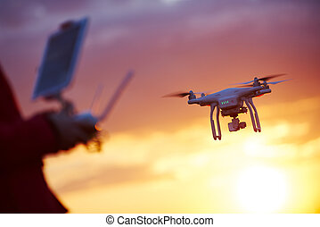 drone pilotage at sunset - piloting flying copter drone at...