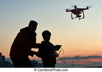 man operating of flying drone at sunset - Man with child...