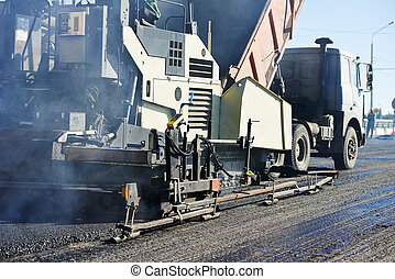 Paver machine laying asphalt, fed by a dump truck - Road...