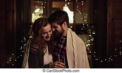 Beautiful hipster couple outside, wrapped in knitted blanket...