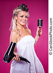 Beautiful smiling woman drying her hair with a blow dryer on...