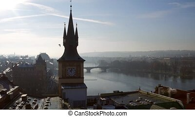 Spired clock tower against Vltava river in Prague on a sunny...