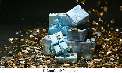 Gold confetti falling on blue gifts boxes on black...