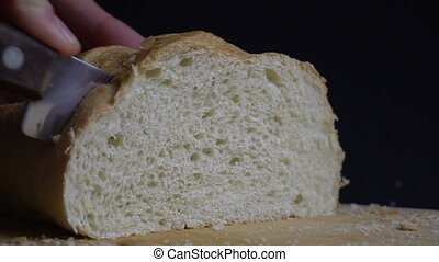 Male hand cutting loaf of bread. - Male hand cutting fresh...
