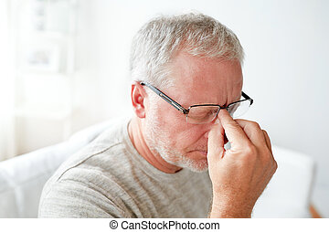 senior man suffering from headache at home - healthcare,...
