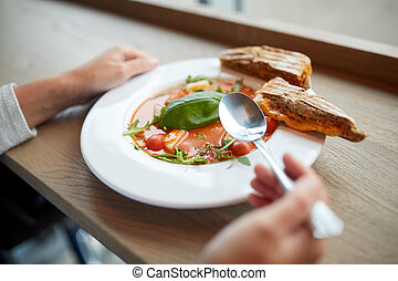woman eating gazpacho soup at restaurant - food, dinner,...