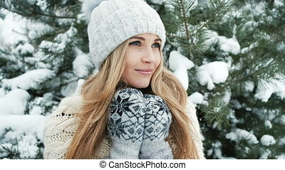 Blonde woman standing in winter landscape near fir tree....