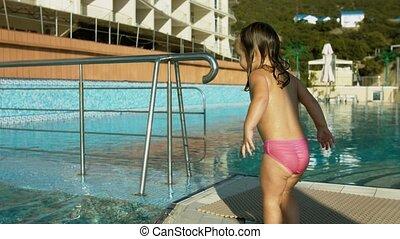 Two little girls having fun in the swimming pool