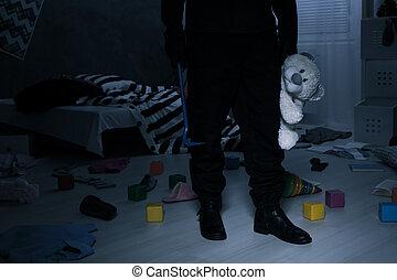 Burglar holding a teddy bear - Burglar standing in dark...