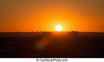Sunset over the industrial city. Sun close-up. Karaganda,...