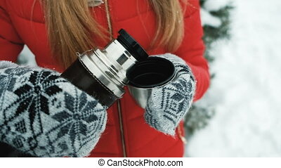 Young woman warm with tea from thermos on frost outdoor. We...