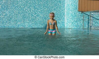 Little girl in the swimsuit fooling around at the swimming pool