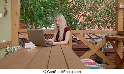 Young woman work outdoor in cafe using laptop. Something...