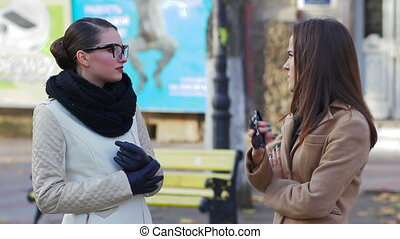 two young women talking on the street in autumn