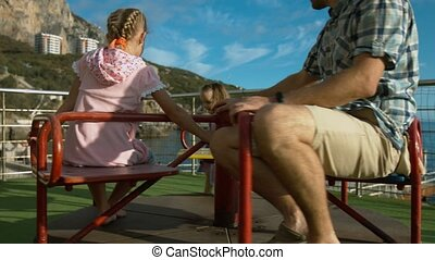 Little girl spinning on carousel dad and older sister outdoors