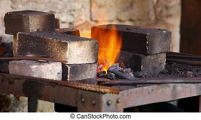 Forge flames close to - Blacksmith heats the iron in the...
