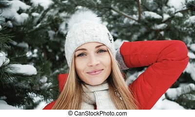 Blonde woman taking part in winter photo shoot near fir tree