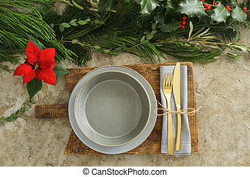 Christmas place setting with golden silverware, holly and...