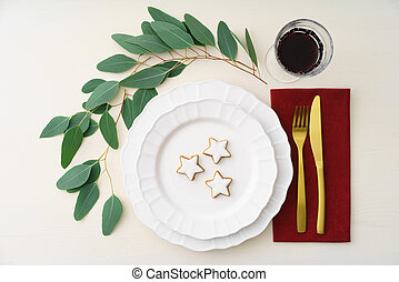 Christmas place setting with golden silverware, eucalyptus...