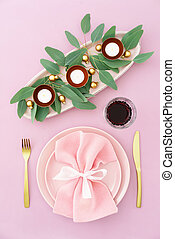 Christmas place setting in pink with golden silverware,...