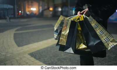 Christmas shopping. girl goes with packages from shop -...
