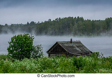 The traditional Russian log hut in poor condition on the...