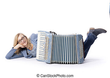 woman in blue with glasses lies behind accordeon and smiles...