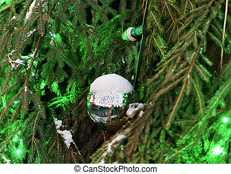 Glittering Christmas ball on green Christmas tree covered...