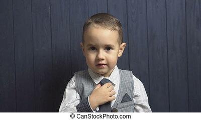 Elegant Kid Boy Correct His Tie - Serious kid boy correcting...