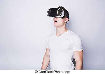 Young man trying vr goggles. Boy sees something astonished...