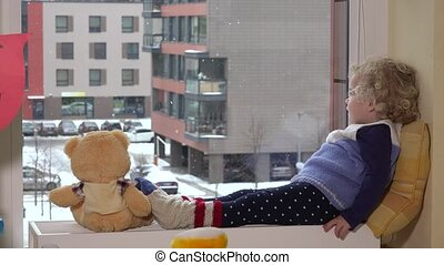 Toddler girl child talk with teddy bear excited to see snow outside