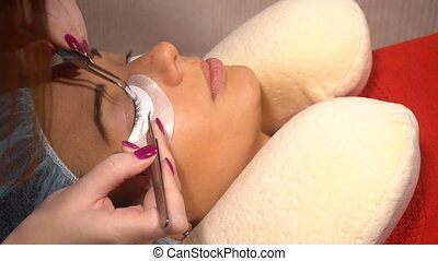 Beautiful young woman doing eyelash extension in beauty...