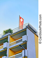 House with Swiss flag in Ascona of Ticino in Switzerland -...