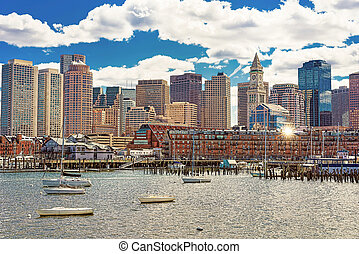 Floating boats and ships in front of the Boston skyline -...