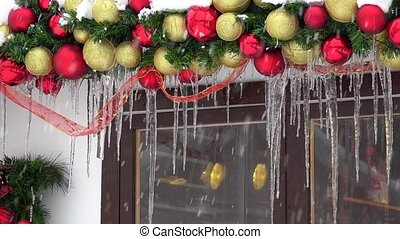 Christmas toy decorations covered with icicle and snow. Blizzard snow falling