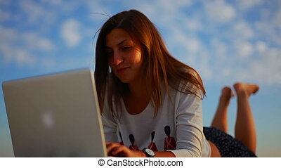 female freelancer writing an article on a laptop outdoor against the blue sky