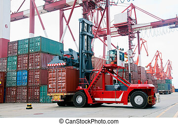 Container forklift - A forklift crane parked next to stacks...