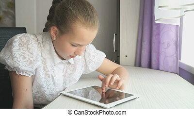 Teenager girl uses a digital tablet at the desk - Teenager...