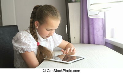 Teenager girl uses a digital tablet at the desk - Teenager...