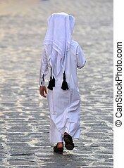Figure of unidentifiable Arabic boy in white thobe walking...