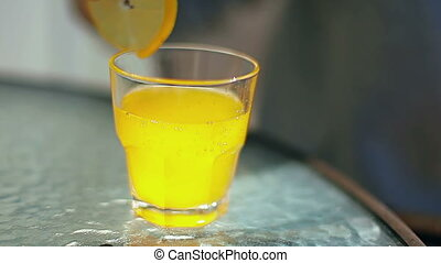 female hands adding lemon and a straw in a glass with a yellow cocktail
