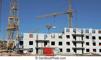 Construction crane delivers a cement for builders - The...