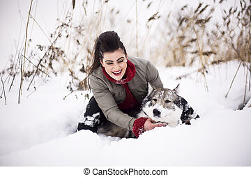 Young fashion girl walking playing with husky dog outside in winter snow park, having fun together, lifestyle people concept