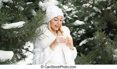 Beautiful blonde eats tangerine against background of winter landscape